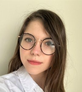 Head and shoulders shot of Kristyna, wearing glasses and a white shirt