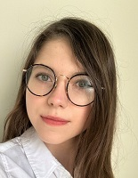 Young woman with round glasses and long brown hair