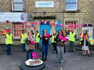 Buxton Street by Street coordinators and volunteers wearing high-vis yellow jackets and waving flags outside Connex building.