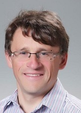 Headshot of Pau Davies wearing glasses and checked shirt on light grey background